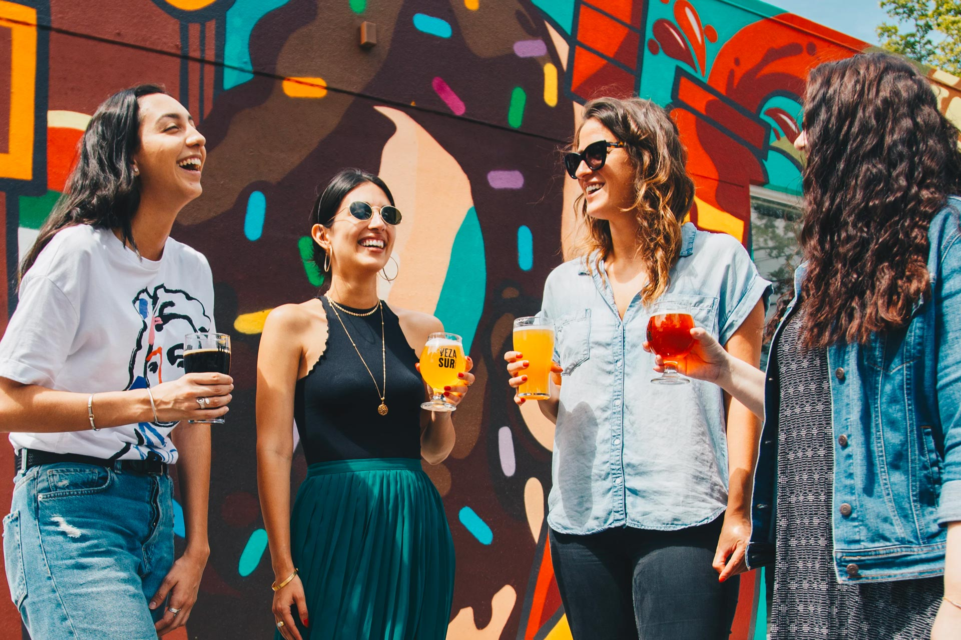 Four women having good time with colorful cocktails and good laugh